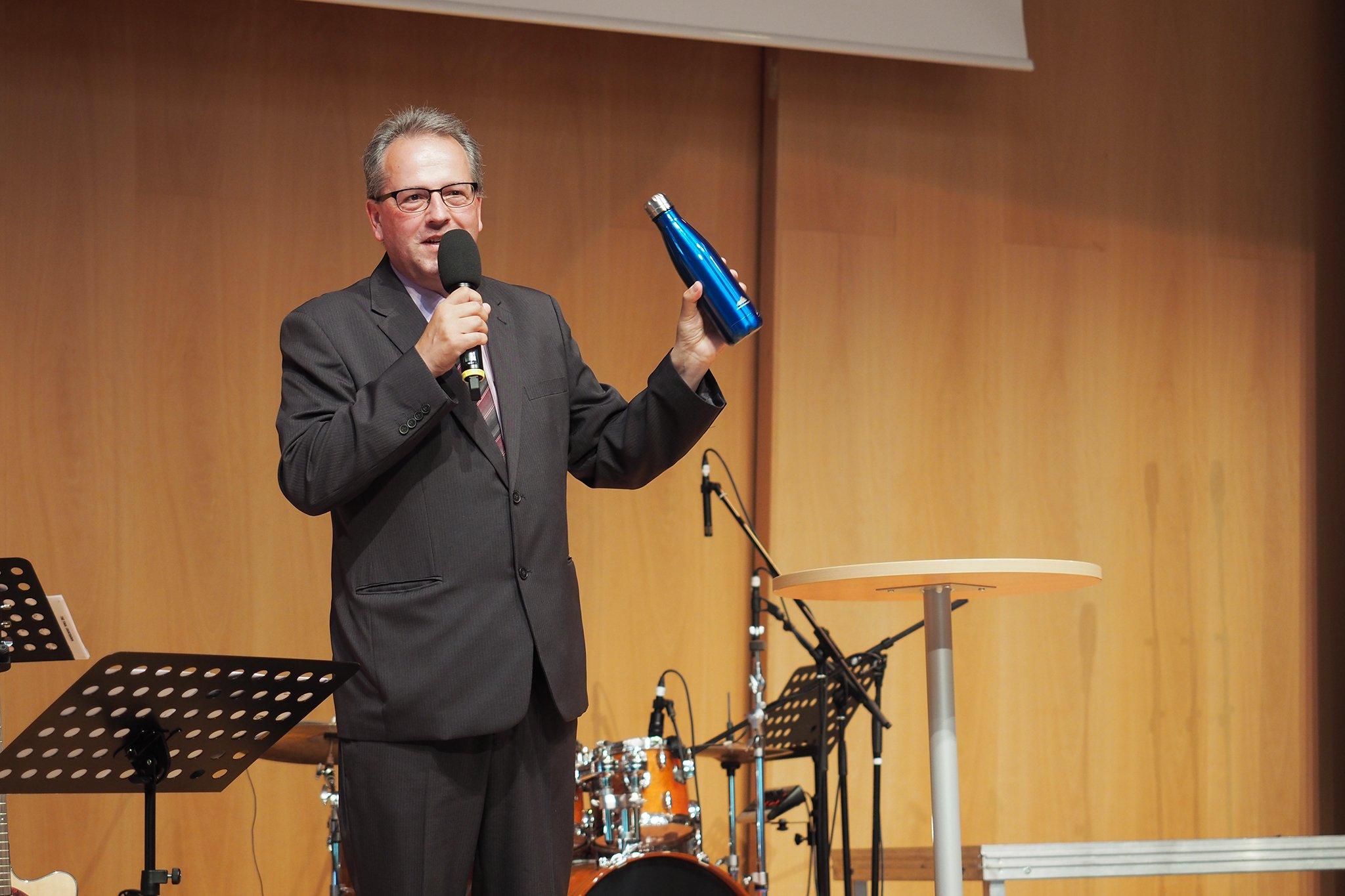 tsc-Jahresfest 2019: Dr. Benedikt Walker schenkt den Absolventen eine Trinkflasche
