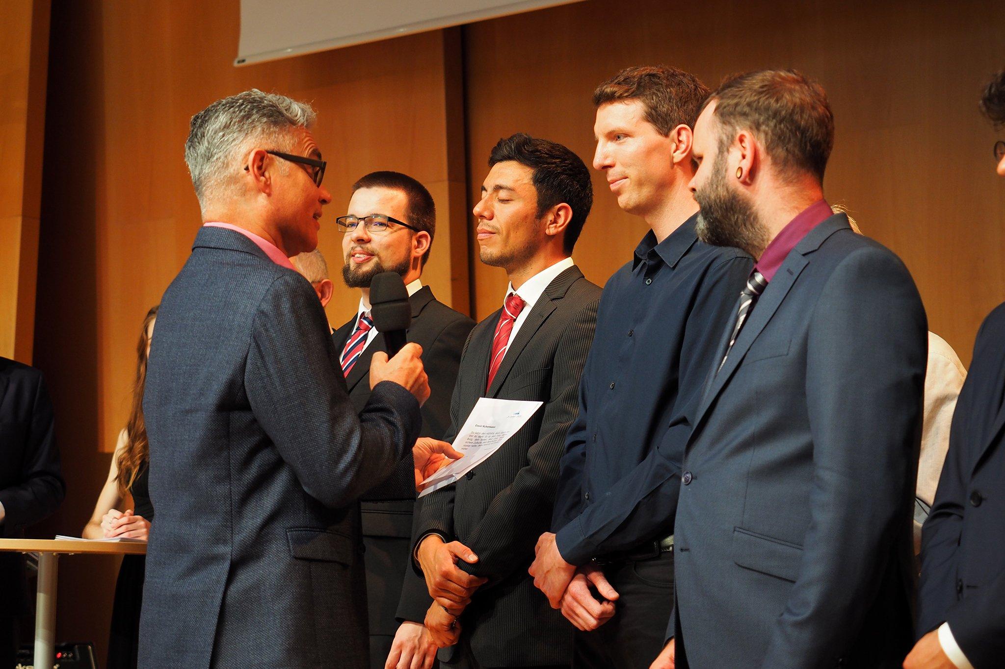 tsc-Jahresfest 2019: Der tsc-Dozent Reiner Bamberger spricht dem tsc-Absolventen David Achermann einen Bibelvers zu.