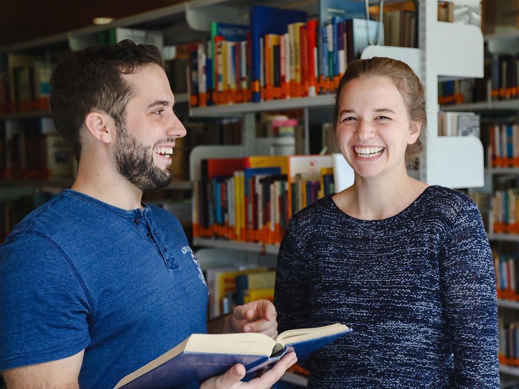 tsc-Bibliothek: Student und Studentin tauschen sich aus.