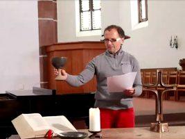 Dr. Andreas Loos, Dozent des tsc, spricht die Einsetzungsworte des Abendmahls in der Kirche St. Chrischona. Die Mitarbeitenden nehmen per Videotelefonie daran teil.